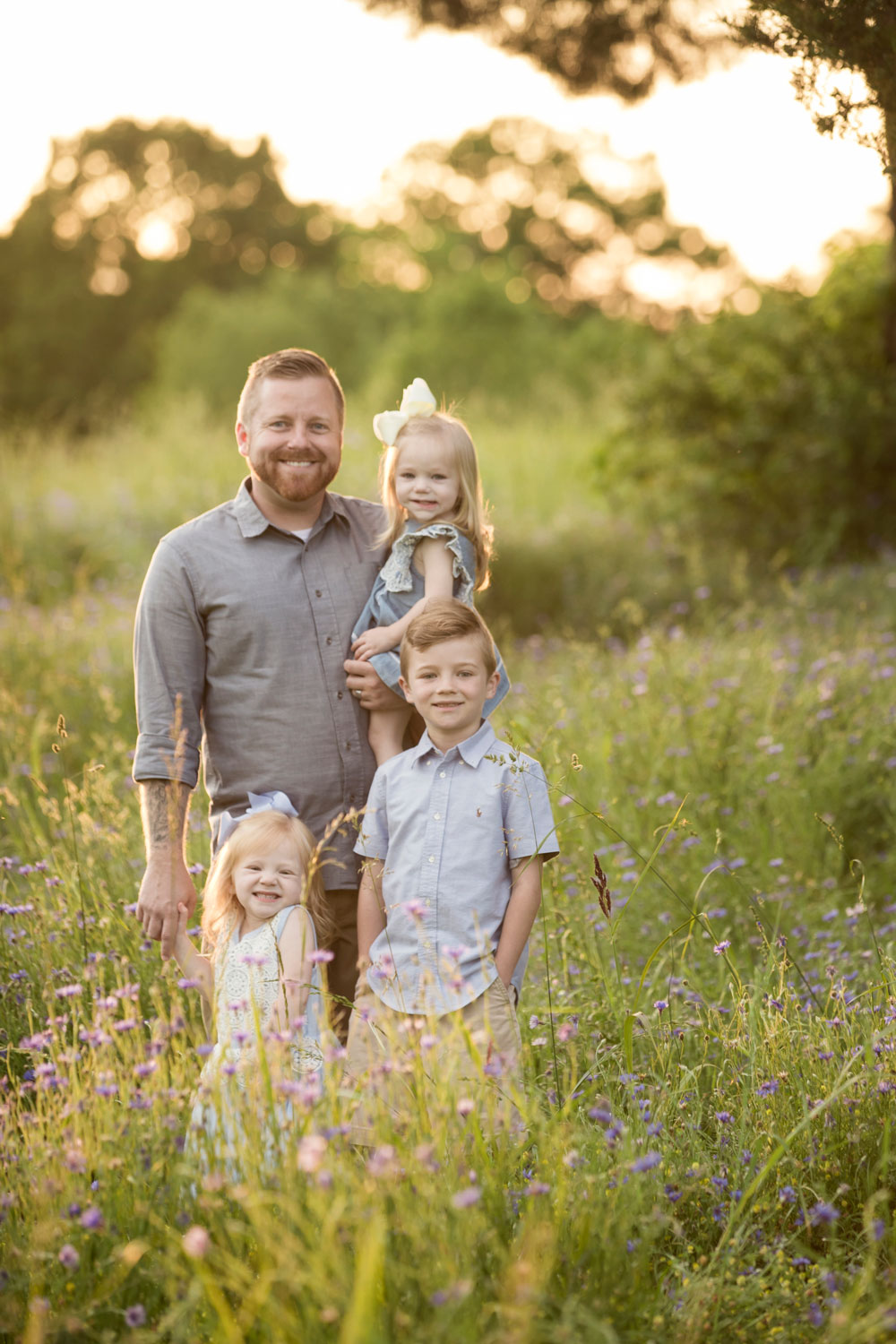 Dad poses with his three kiddos in Maryville field of flowers.