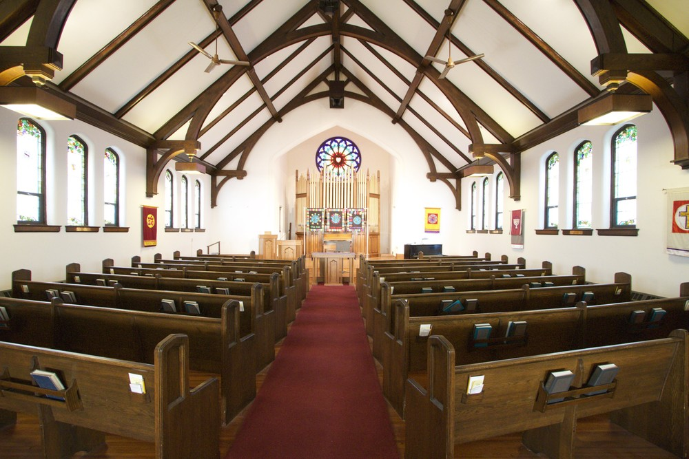A view of the Sanctuary from the rear of the main space towards the front showing the beautiful wood beams, pipe organ, and Rose Window. Each side of the aisle features eight full pews with one half pew nearest the pulpit.