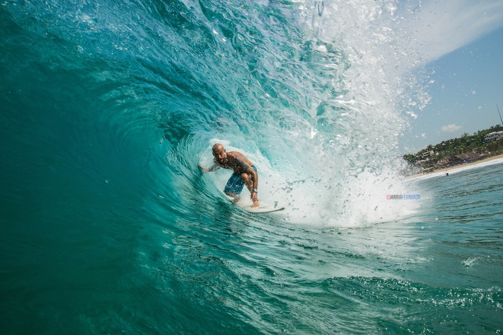 Brazilian surfer, Thiago Testinha traveling through a small blue barrel.