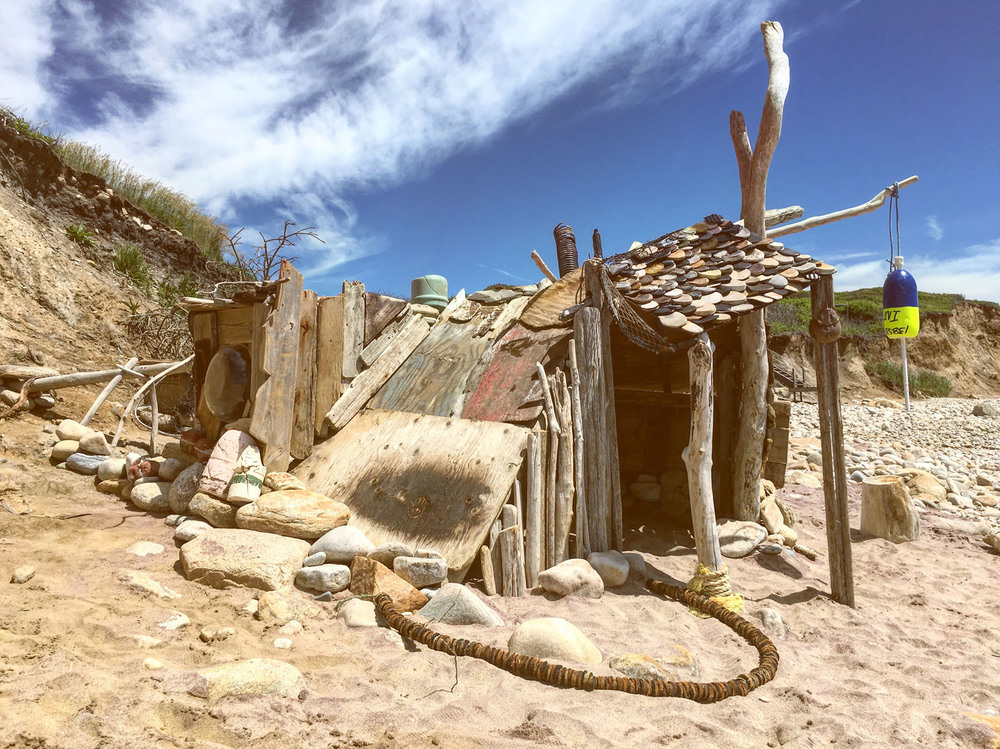 "Amsterdam Beach Shack    found objects, driftwood, buoys, bricks, shoe soles, salad bowls, branches  20' x 12' x 8'  2016  on location at Amsterdam Beach, Montauk, NY. June 2016  (Available as archival digital print, 16"" x 20"", edition of 50)"