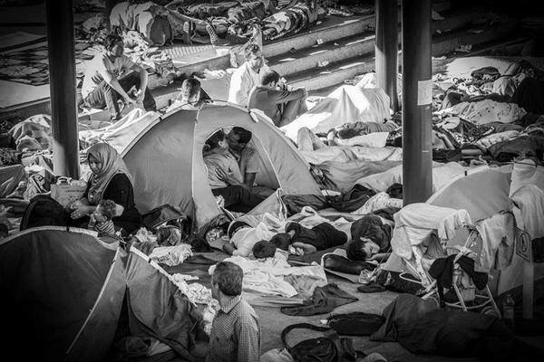 Syrian refugee couple stealing a kiss under a tent. taken at Budapest's Keleti train station on August 30 by Hungarian photographer Zsíros István ( Laleh Khalili )