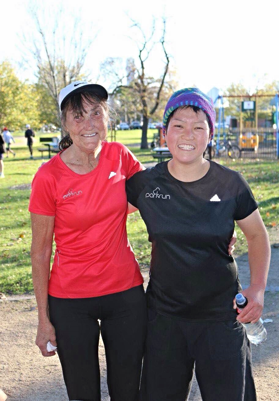 Such happy faces on Albert Melbourne regulars, Jenny and Miwa, turned parkrun tourists modelling their 50 and 100 milestone t-shirts