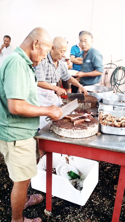 Uncles chopping roast pork for the hungry ghost festival