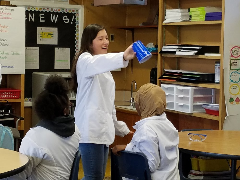 A 10th grade CAPTS student performing a chemistry magic trick for 5th graders
