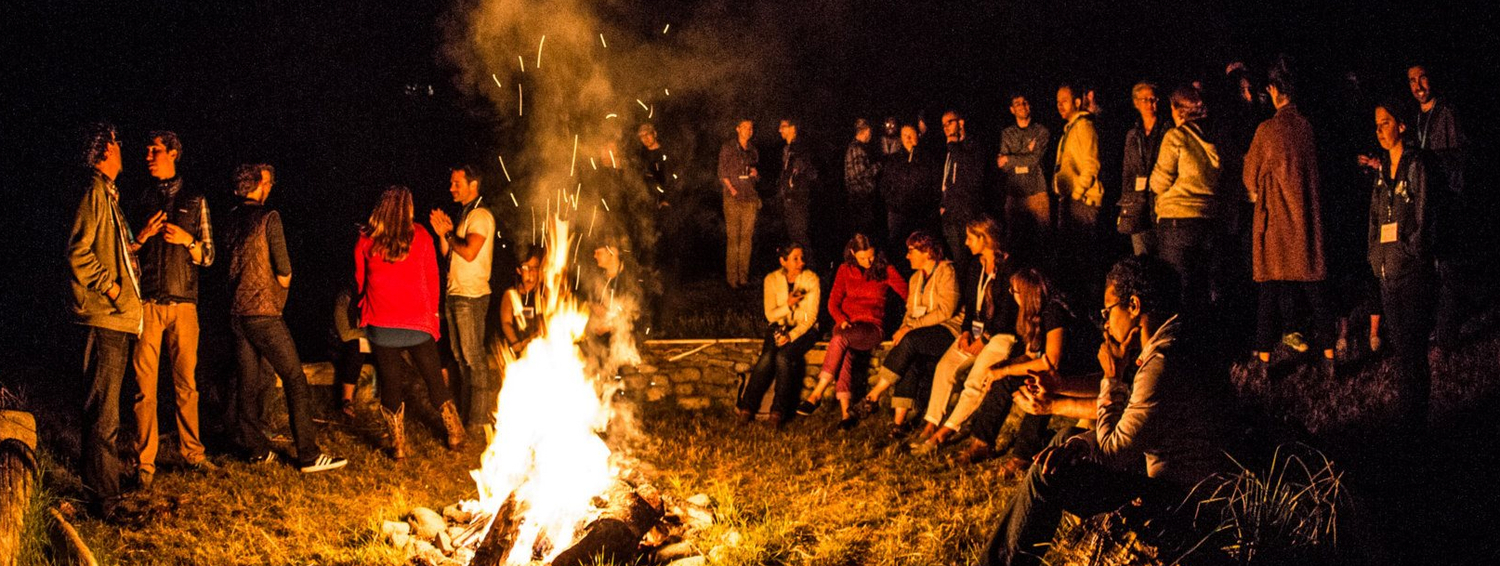 Web of change participants around bonfire.