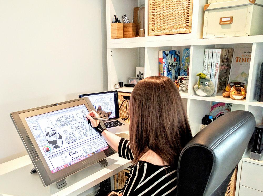 Jo Ley working on her comic for Mikaela Gilbert's Chatter Eggs. Spot the kitten!