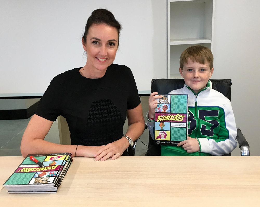 Jo Burston with young entrepreneur Ben Breeze holding a copy of the book