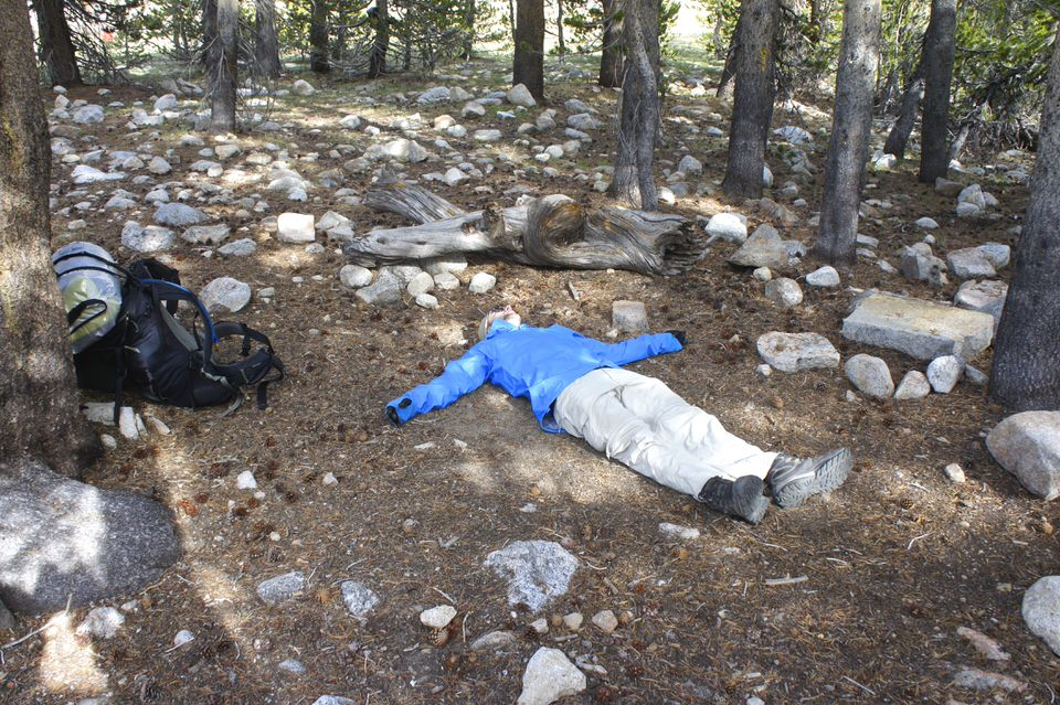 tired-hiker-lying-on-ground-at-camp