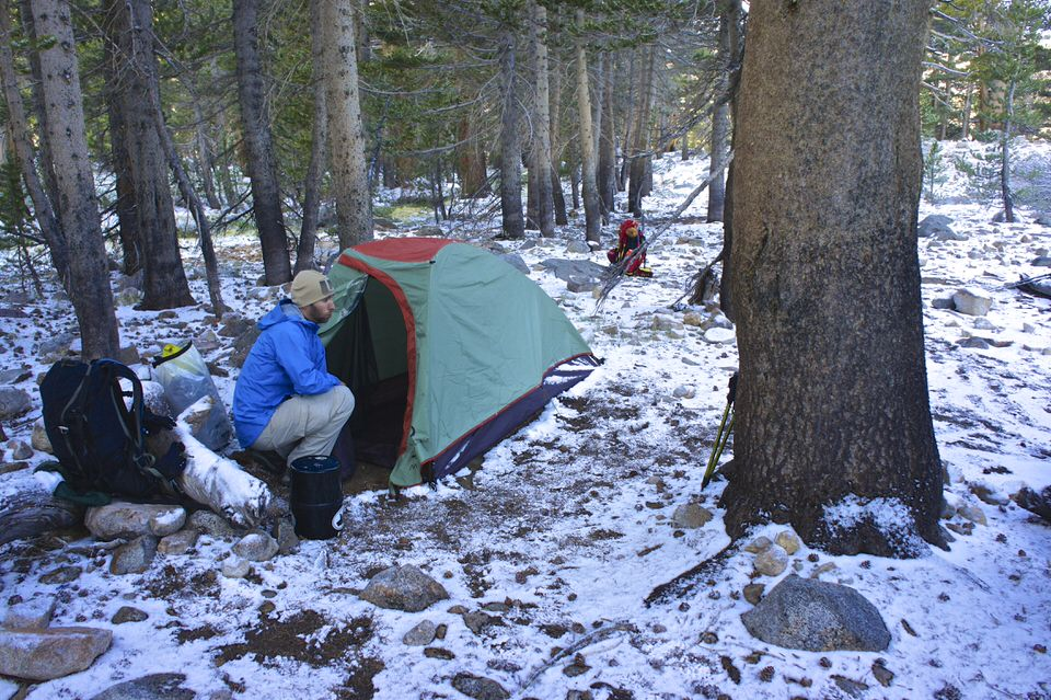 boy-sitting-outside-tent-at-snowy-campsite