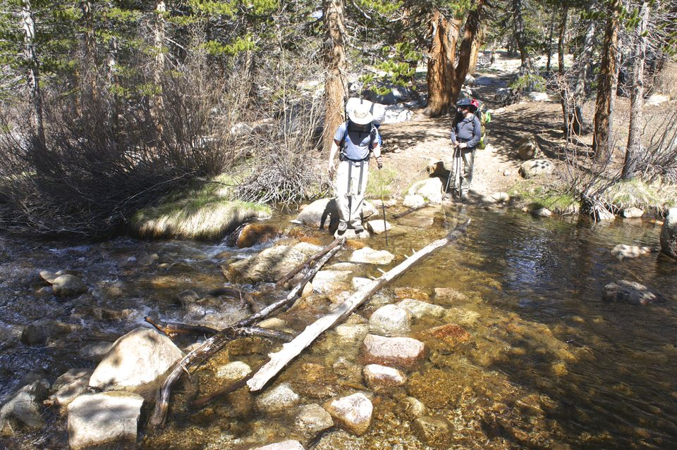 backpackers-walking-across-logs-on-a-stream