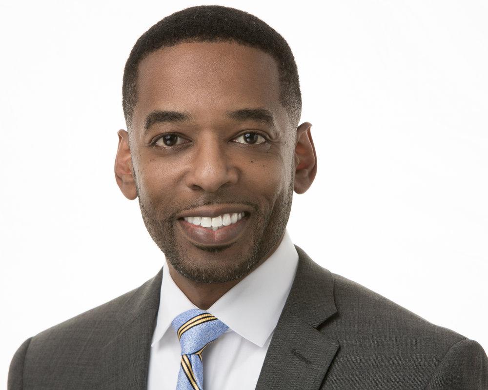 Corporate Headshot of Jamar Robinson Grey Jacket Blue and Yellow Tie