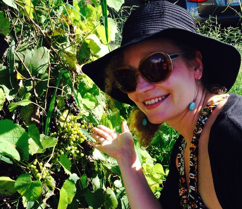 In the vines, gesturing to the tropical grapes