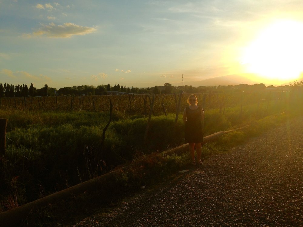 The sun setting on some vineyards and I, in Mendoza, Argentina. Photo by Gabriel Manzo
