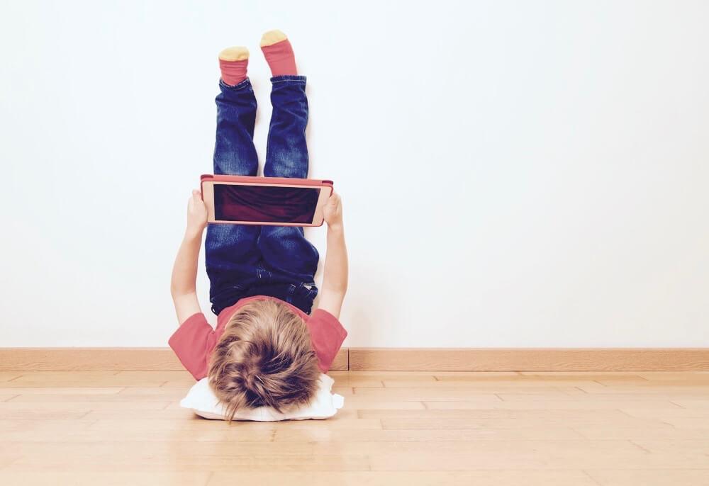 Kind mit Tablet, das am Boden liegt und Füße in die Luft streckt