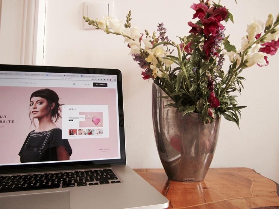 Laptop mit Squarespace-Homepage, rechts daneben steht Blumenvase