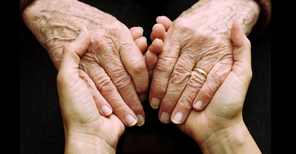 old sick womans hands with young womans hand