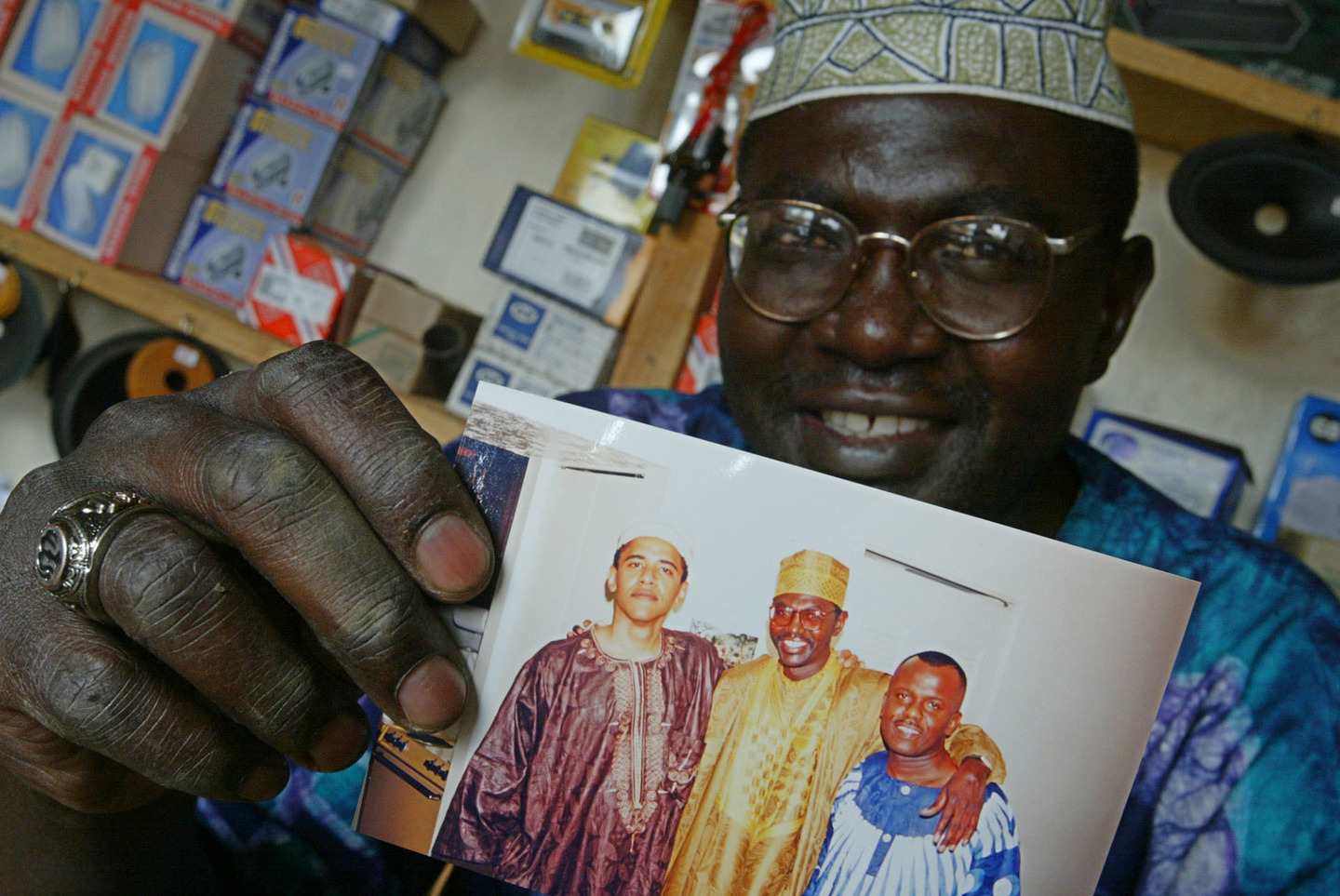 Malik Obama, the older brother of Barack Obama, holds an undated picture of Barak, left and himself, middle, and an unidentified friend in his shop in Siaya, Kenya, in 2004