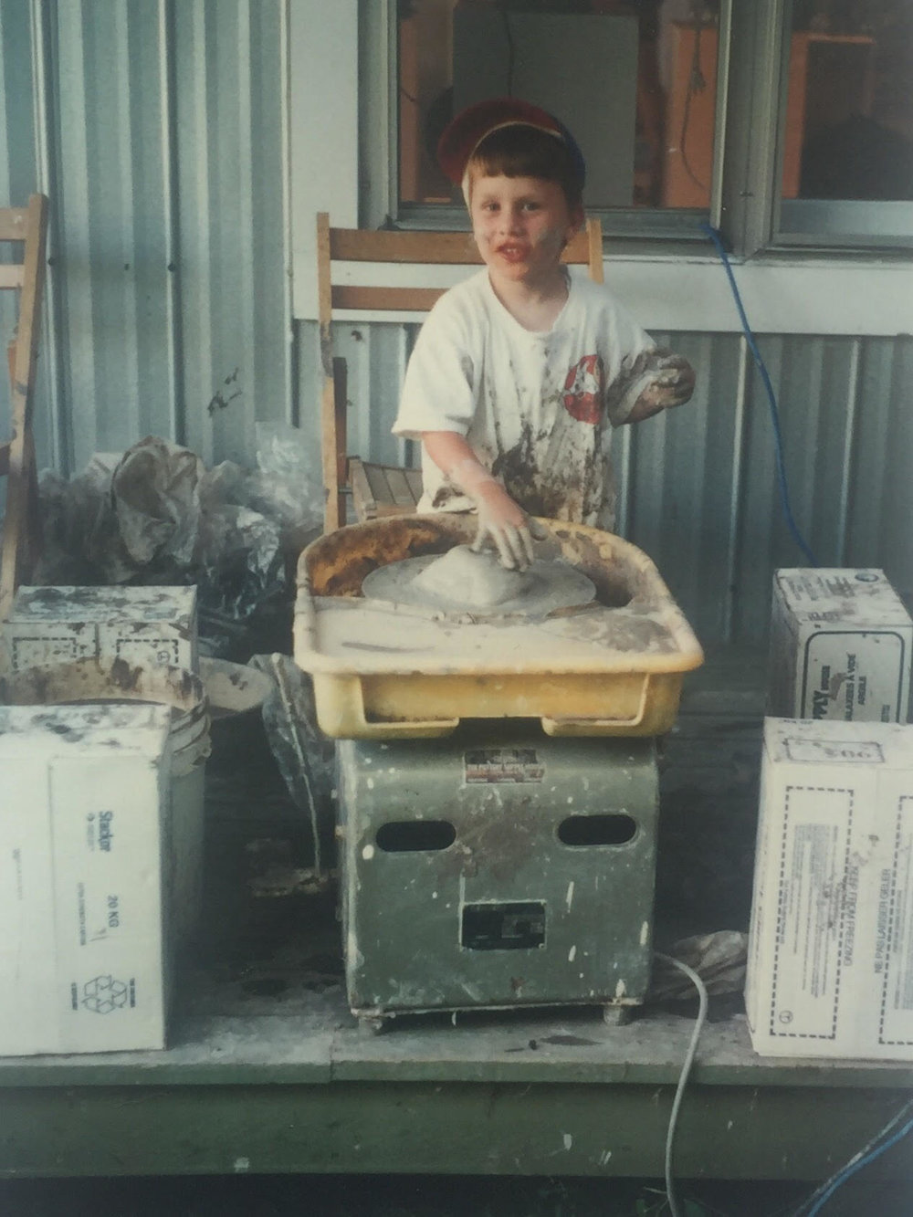 Gab at seven years old, tinkering with his dad's pottery wheel