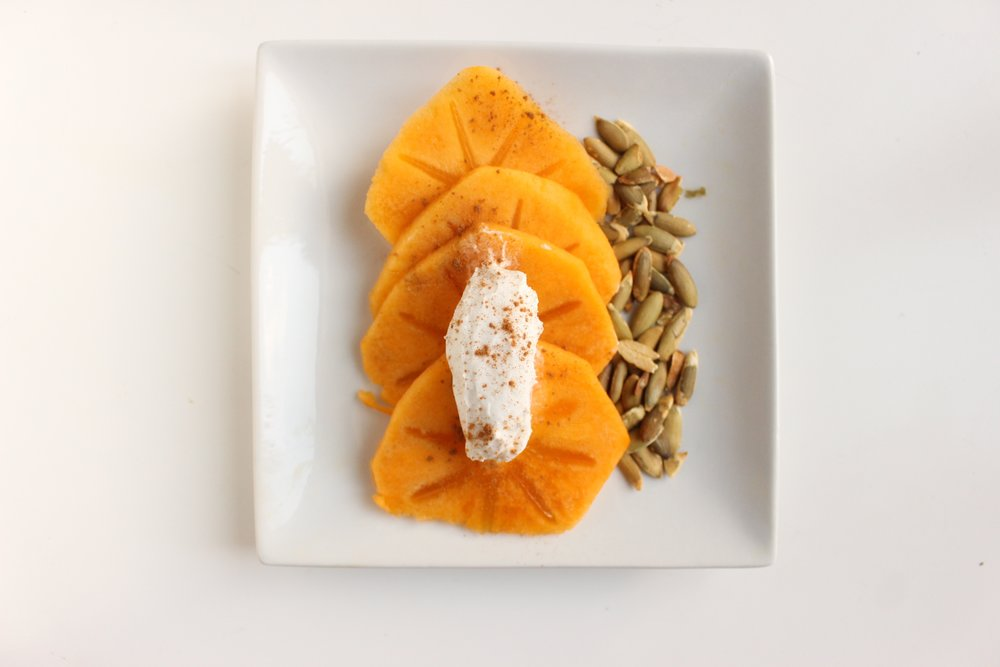 Persimmons with coconut cream and pepitas | Me & The Moose. Dress up your fruit with some good fat from coconut cream and some crunch from pepitas. #meandthemoose #whole30 #whole30recipes #persimmons #snacks #snackrecipes
