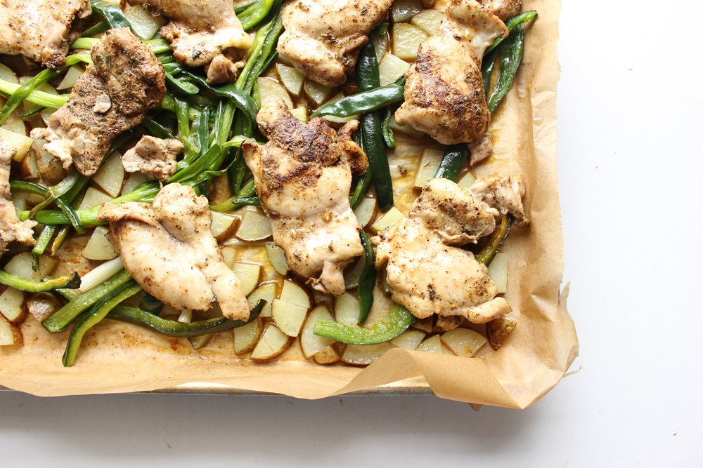 Sheet pan dinner: chicken thighs with poblano peppers, potatoes, and scallions.