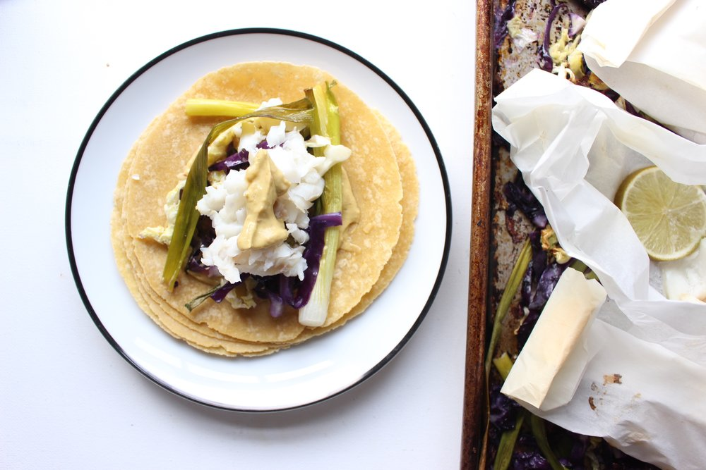Roasting the fish, scallions, and cabbage on a sheet pan make an easy weeknight taco night with almost no clean up.