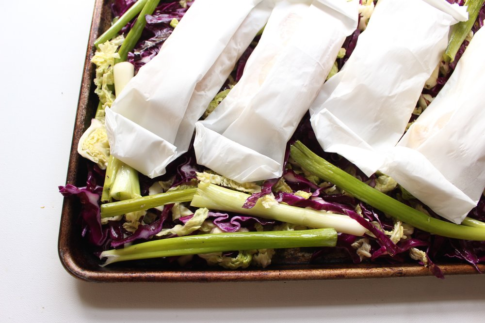 Wrapping the white fish in parchment packages helps retain their moisture while also letting the cabbage and scallions get roasted and crispy. It also decreases the mess even more.