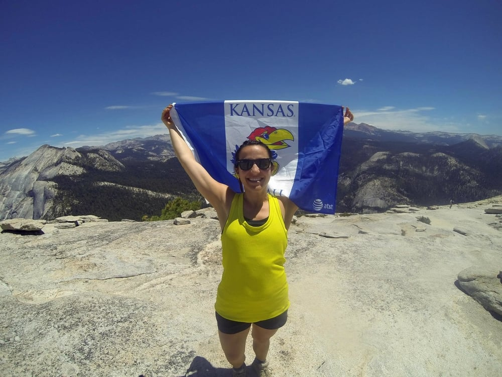 Blair showing Kansas Pride at the top of Half Dome, Yosemite.           Photo Credit: Erik Anderson