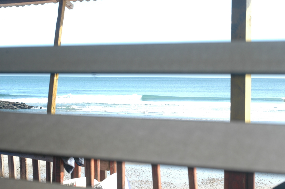 a waves at Maderas Beach, Nicaragua through a window at Los Tres Hermanos hostel