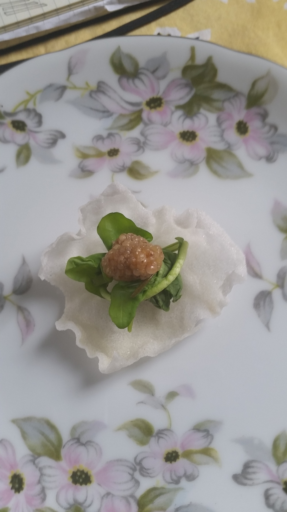 Pickled Mulberry on a puffed rice cracker with nest of arugula.