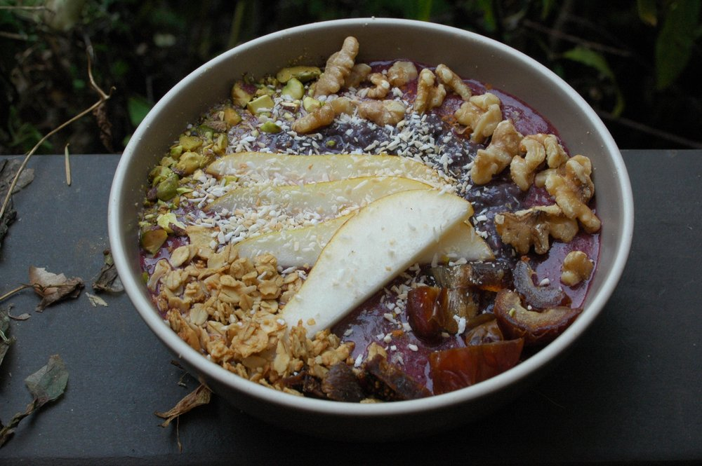 Berry Banana smoothie bowl with pear, walnuts, pistachios, dates, figs, granola, shredded coconut and chia pudding.