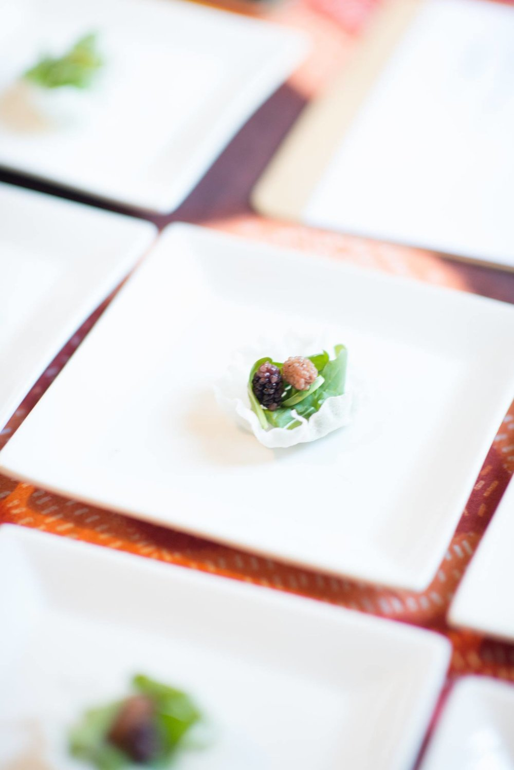 The Amuse Bouche of our Botanical Imperialism Curated Feast, a pickled mulberry on rice puff with arugula.   Photo courtesy of  Victoria Smith