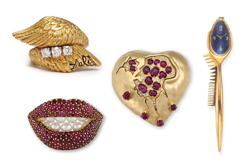 All Salvador Dalí pieces, from left to right:  Gold Angel Wing ring  (1950),  Ruby lips brooch  (1958),  Pomegranate Heart  (1950),  Watch brooch  (unknown).