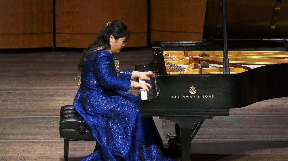 """下半场的开始,和观众交流、和观众介绍来自中国的作品,已经成为佳鑫在舞台上的惯例。佳鑫在舞台上也能够感受到,他们在静静地聆听这首优美的中国作品,感受这首《夕阳箫鼓》中用钢琴弹奏出的中国乐器的声音。     今天的演出,无论是曲目设计,抑或是东方元素的呈现,都是佳鑫精心挑选与设计,不同类型、不同风格、不同地域、不同时期、不同节奏的曲目也分别代表了佳鑫在不同的时间里想要表达的内心和想要传递的情感。     """"佳鑫是第二次来到华盛顿,  但它对佳鑫来说却一点不陌生。"""