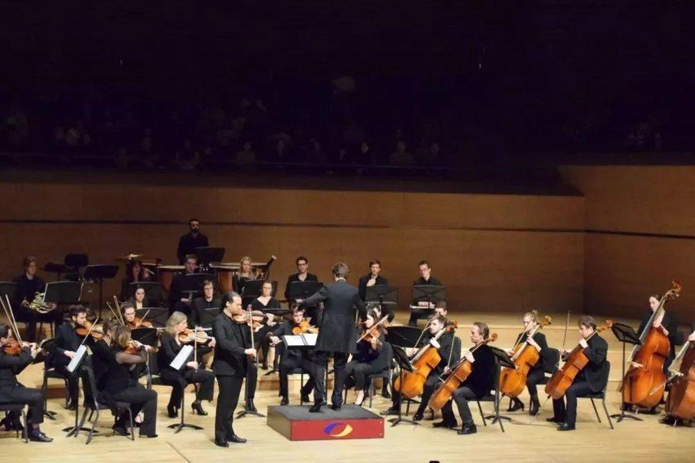 """佳鑫还非常喜欢的,是圣桑的《回旋随想曲》和马斯奈的《泰伊斯冥想曲》,这也是乐队首席Romuald Grimbert Barre担任独奏的两首作品。佳鑫觉得,""""他的触弦温暖人心,音乐的歌唱性也很强,一瞬间就联想到了自己,独奏演奏家很是希望把自己对作品的理解,通过乐器当做桥梁,将自己的人生和经历用双手描绘成一段故事,而观众也从中聆听到自己的人生经历,就这样用音乐触碰到音乐家与观众的内心。""""     佳鑫与工作人员"""