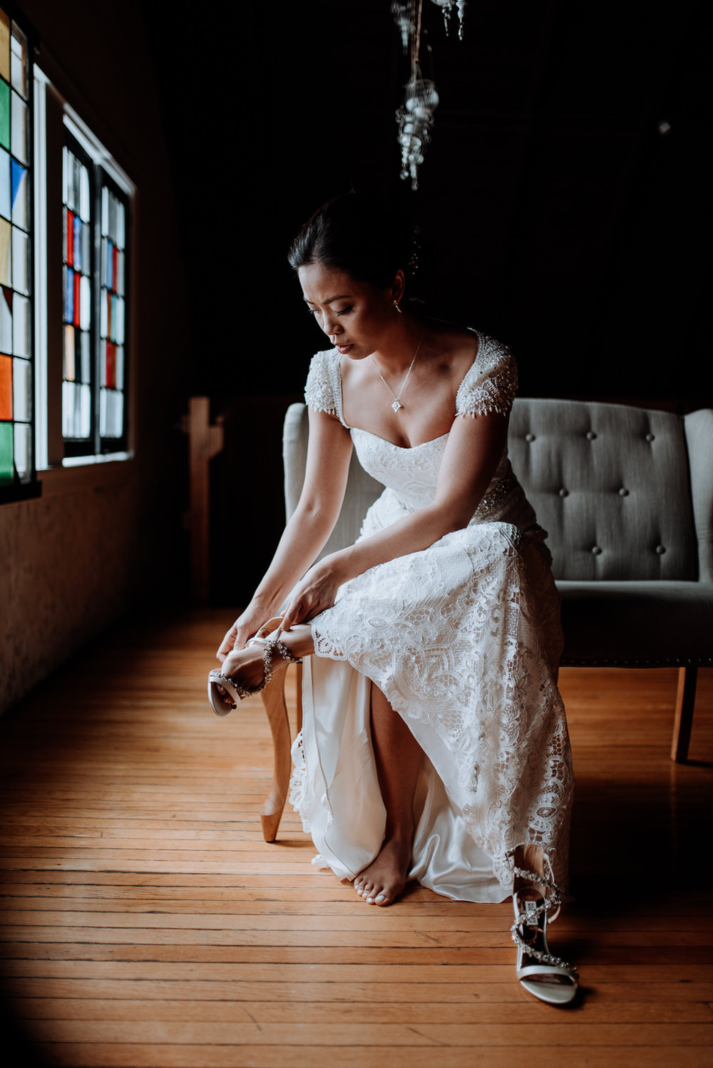 bride puts on wedding shoes upstairs at Red Maple Vineyard Weddi