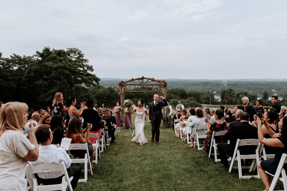 couples walks down aisle at red maple vineyard