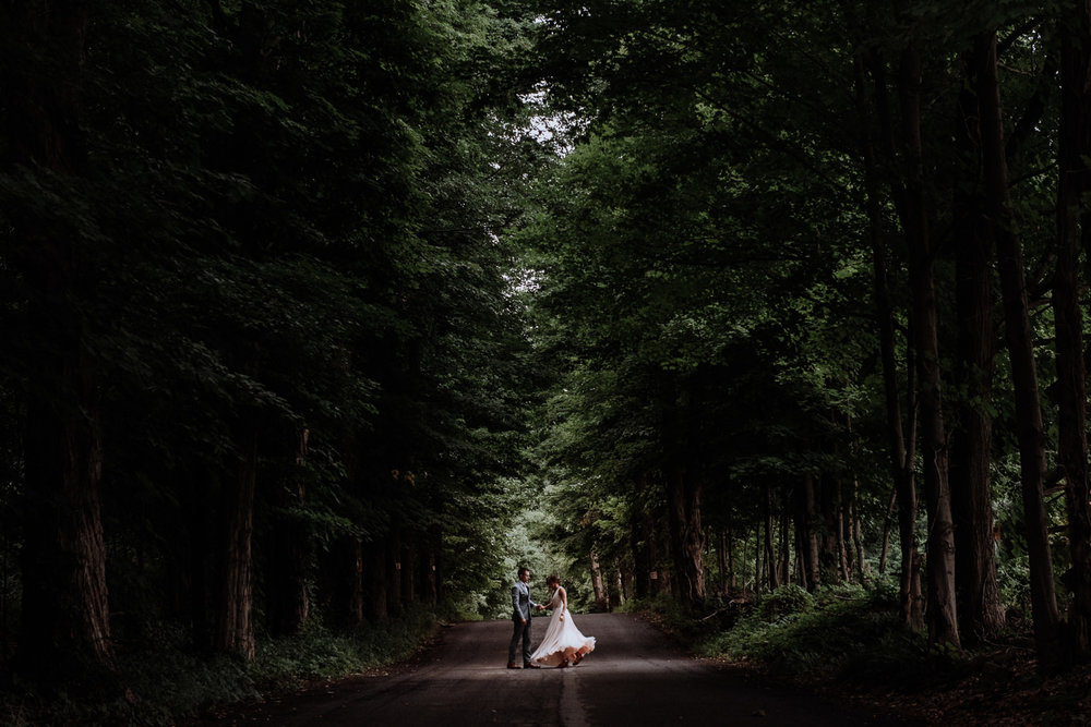 this magical tree lined street at Red Maple Vineyard is the perfect frame for this bride and groom portrait. I love the way her ciffon wedding dress twirls in the breeze as the groom spins her around.