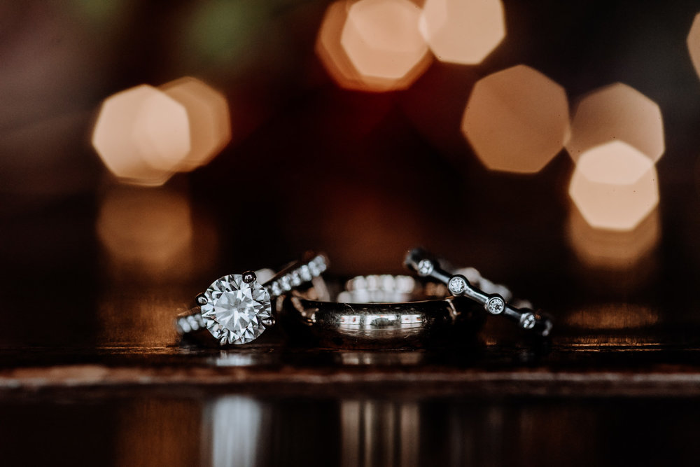 Creative picture of engagement ring and wedding bands at red Maple Vineyard