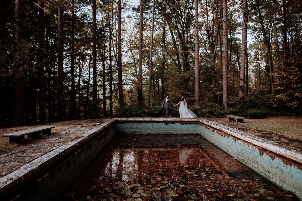 Elegant Bride and groom walk through the forest along the edge of an abandoned pool hidden on the property of their Catskills wedding venue. The autumn leaves are a perfect reminder of why couples like to get married at Onteora mountain house in Ocotber.