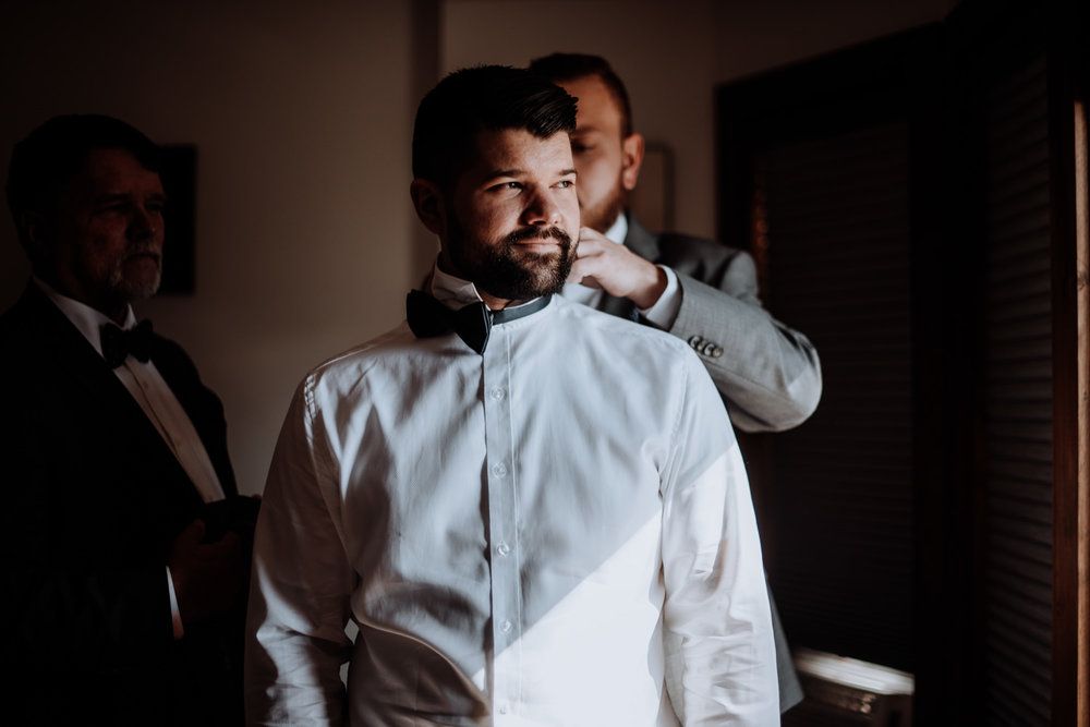 "The Groom's father and best man help him with his black bowtie as he calmly looks out the window towards the Catskill Mountain view he will see when he says ""I Do""."