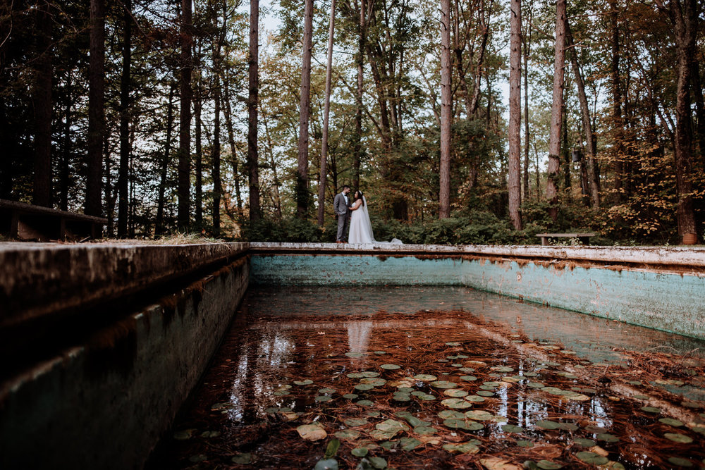 Lily pads and pine needles fill the secret abandoned pool at Onteora Mountain House while the Bride and Groom embrace in a romantic moment..