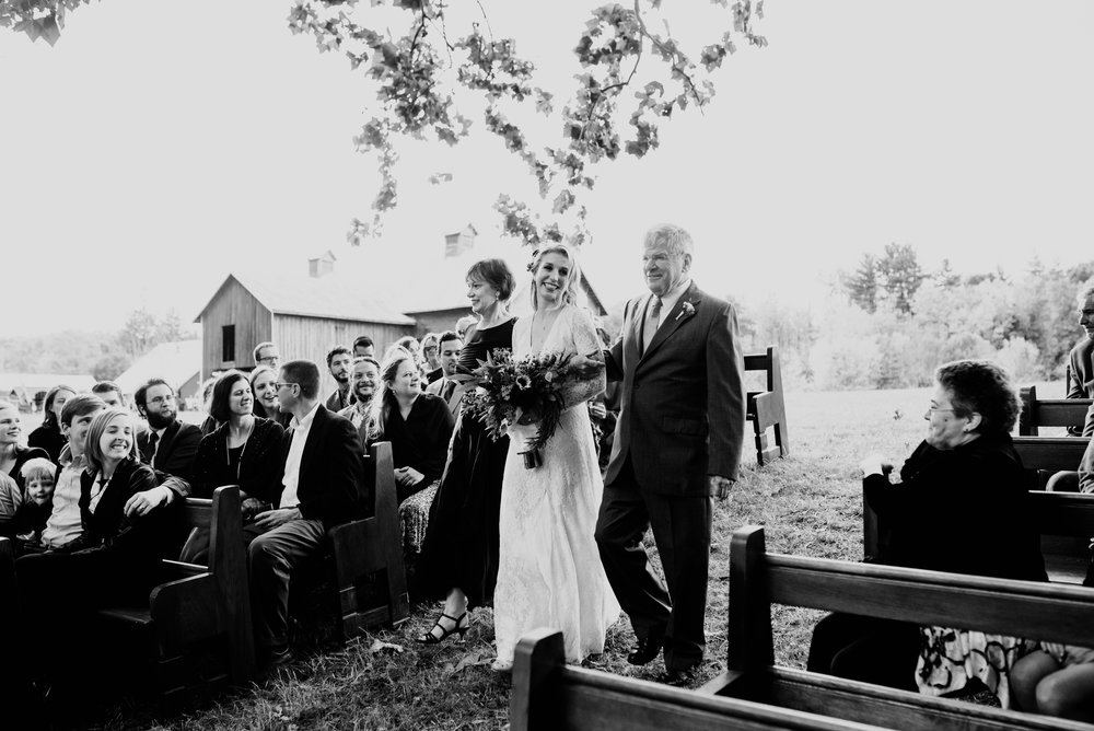 Bride's proud parents walk her between old church pews to her groom waiting on the river bank for their outdoor ceremony