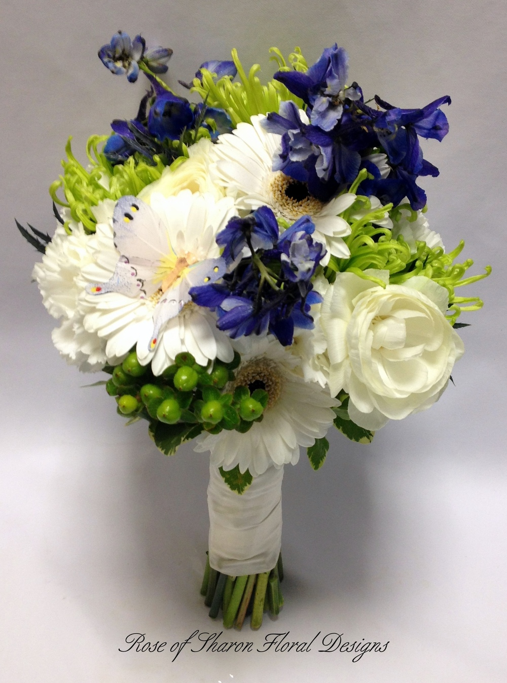 Blue, Green and Ivory Hand-Tied Bouquet featuring Daisies, Mums, Delphinium and Hypericum Berries. Rose of Sharon Floral Designs