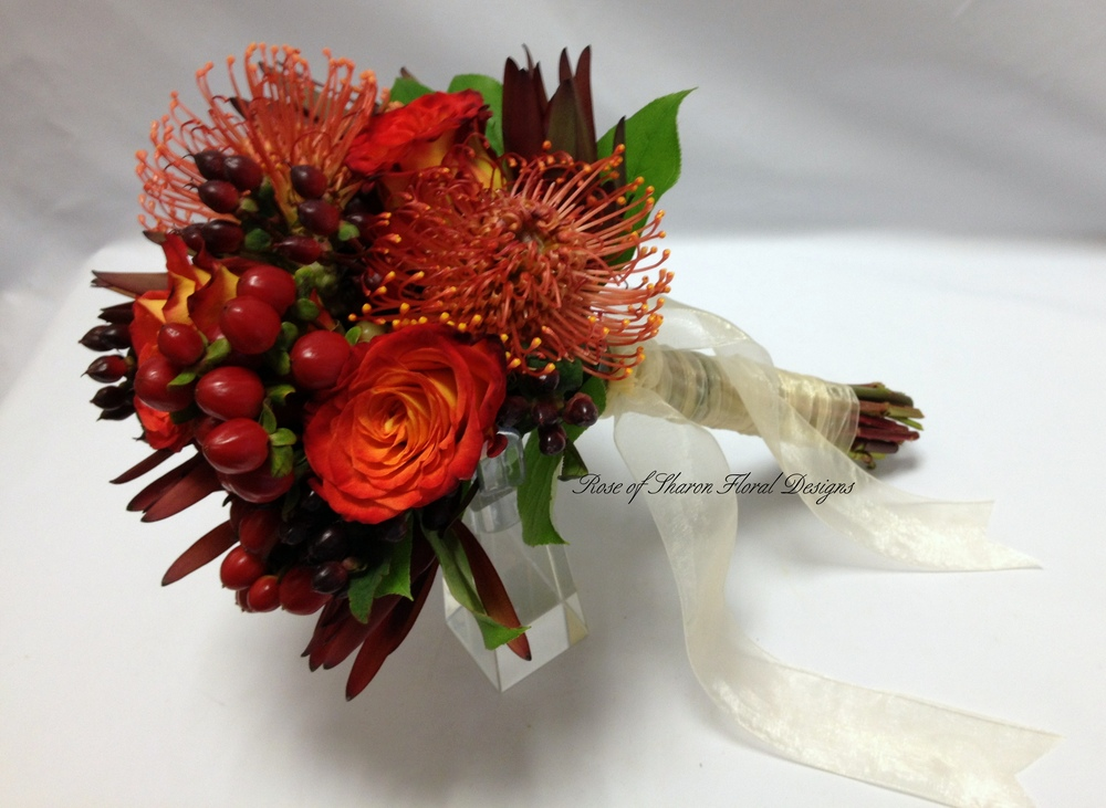 Burgundy and Orange Hand-Tied Bouquet with Roses, Hypericum Berries & Pin Cushion Protea. Rose of Sharon Floral Designs