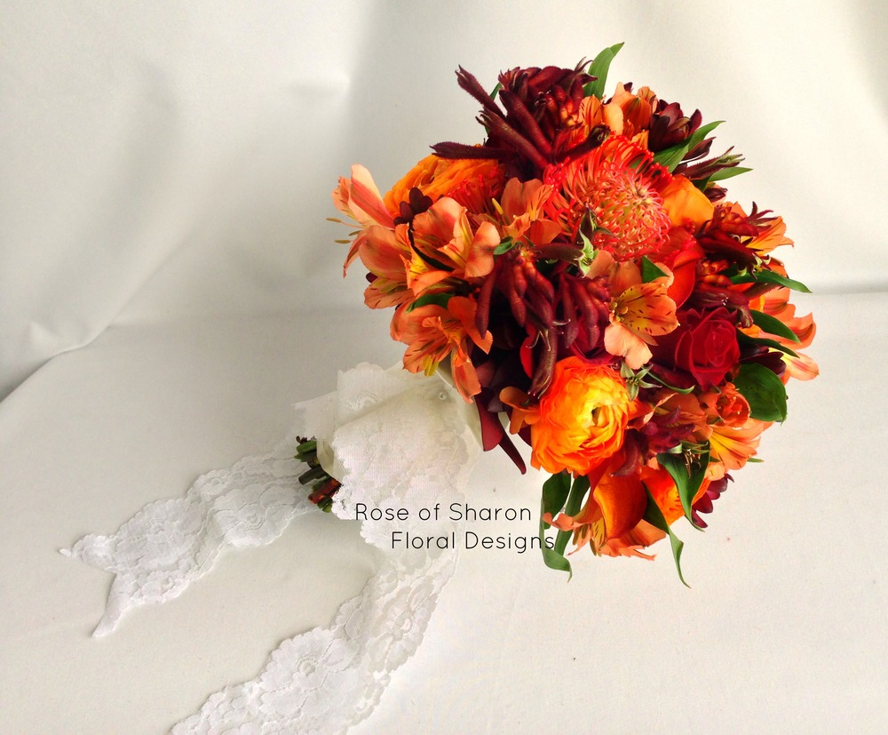 Burgundy and Orange Hand-Tied Bouquet with Alstroemeria Lilies, Pin Cushion Protea, Roses & Calla Lilies. Rose of Sharon Floral Designs