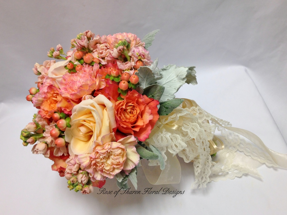 Orange and Peach Hand-Tied Bouquet. Free Spirit Roses, Carnations, and Hypericum Berries. Rose of Sharon Floral Designs
