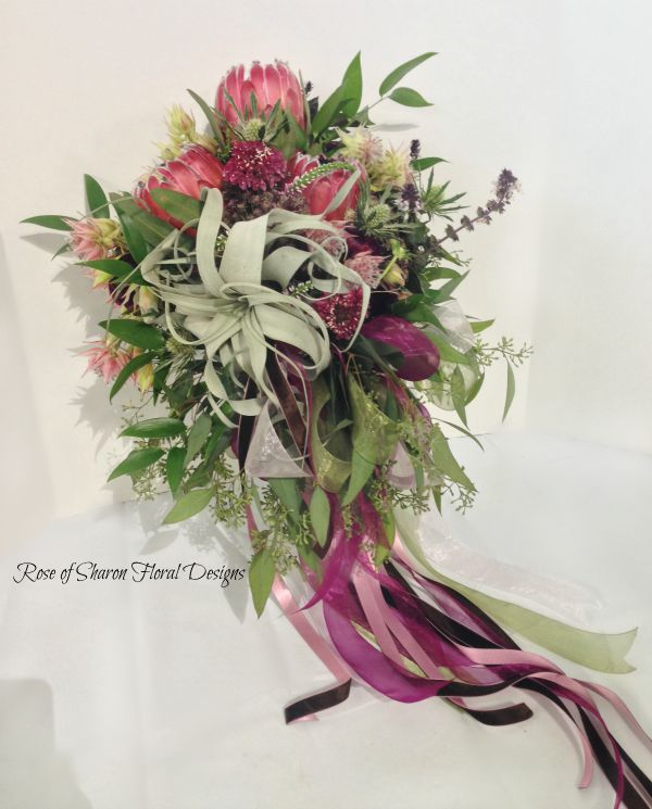 Natural Cascade. Garden bouquet. Pink, plum and green. tillandsia, protea, and eucalyptus. Rose of Sharon Floral Designs.