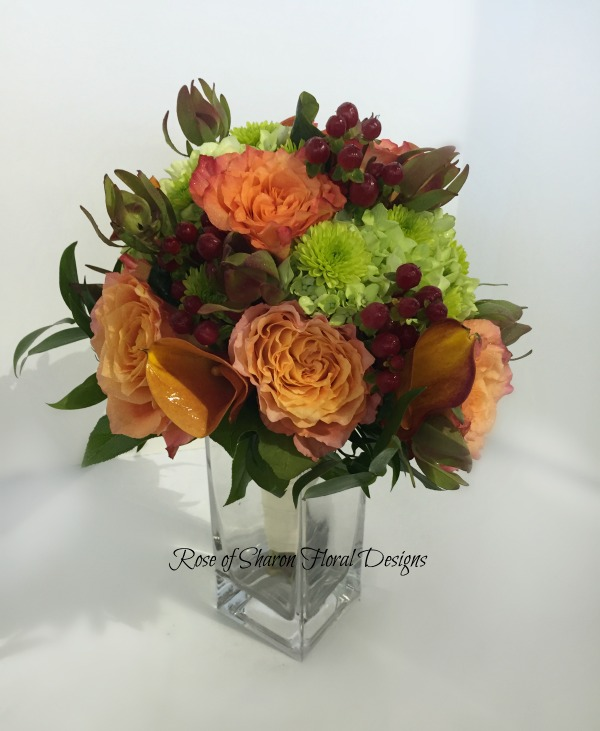 Orange and Green Hand-Tied Bouquet with Free Spirit Roses, Hypericum Berries, Green Button Mums, and Leucadendron. Rose of Sharon Floral Designs
