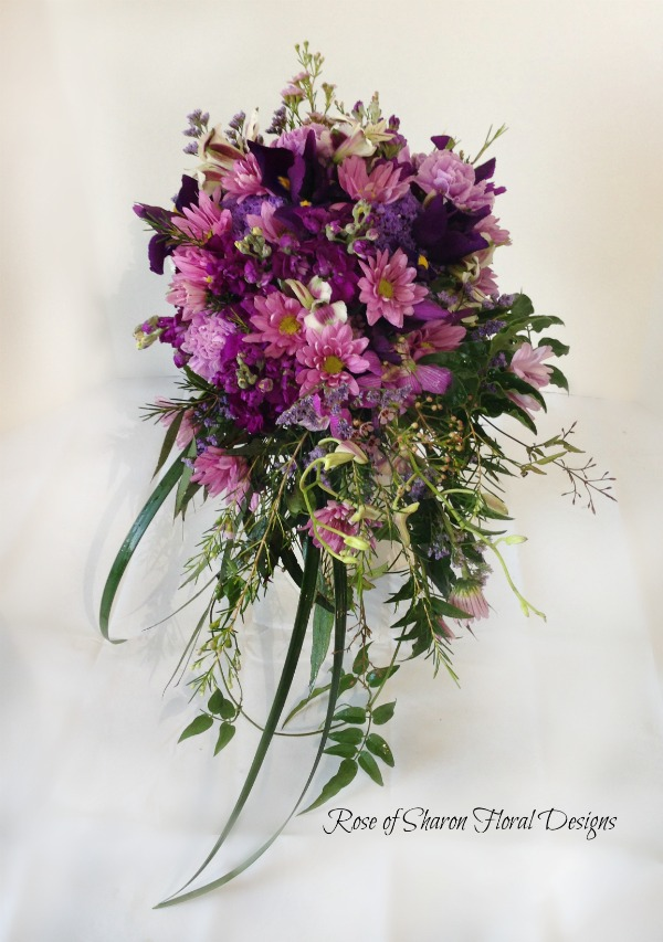 Cascading purple bouquet with daisies, carnations & stock. Rose of Sharon Floral Designs
