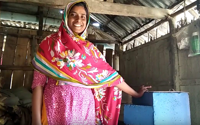 Ms. Salma Khatun stands next to her family's new water filter in Chotto Kupot, Bangladesh.